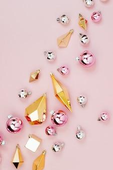 Композиция flat lay holiday со стильными рождественскими блестящими шарами и золотыми кристаллами на пастельно-розовом фоне. плоская планировка, вид сверху