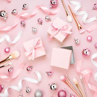 クリスマスボール、ギフト、リボン、化粧ブラシ、パステルピンク色の装飾とフラットレイホリデーの背景。フラットレイ、上面図