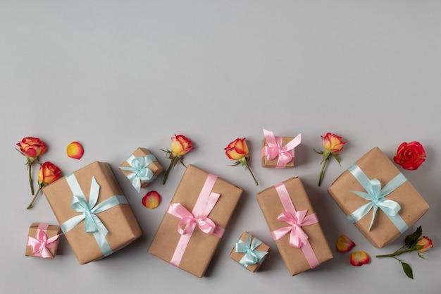 灰色の背景にバラとギフトボックスを備えたフラットレイホリデーコンポジション。女性の日、バレンタイン