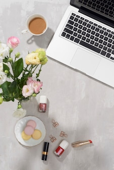 Flat lay home office desk. female workspace with laptop, lisiathus bouquet, macaron, lipstick on white