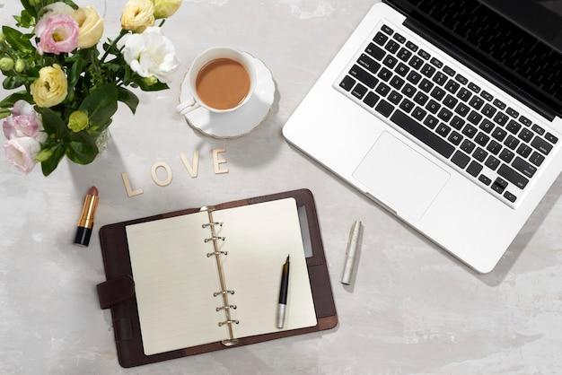 フラット レイアウト ホーム オフィス デスク。ラップトップ、ピンクのトルコギキョウの花束、口紅、日記、白地に愛の手紙を持つ女性のワークスペース