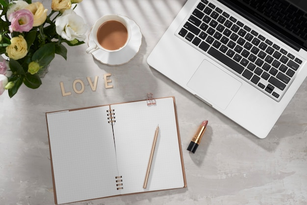 Flat lay home office desk. female workspace with laptop, pink lisianthus bouquet, lipstick, diary and love letter on white