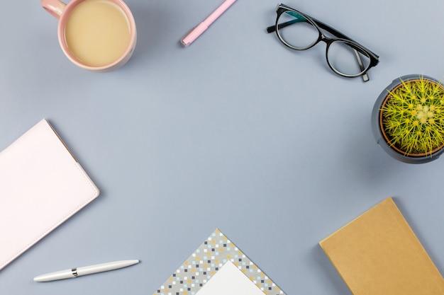 フラットレイアウトのホームオフィスデスク。メモ帳、眼鏡、マグカップ、日記、植物と女性のワークスペース。コピースペース、トップビュー