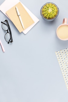 Flat lay home office desk. female workspace with note book, eyeglasses, tea mug, diary, plant. copy space