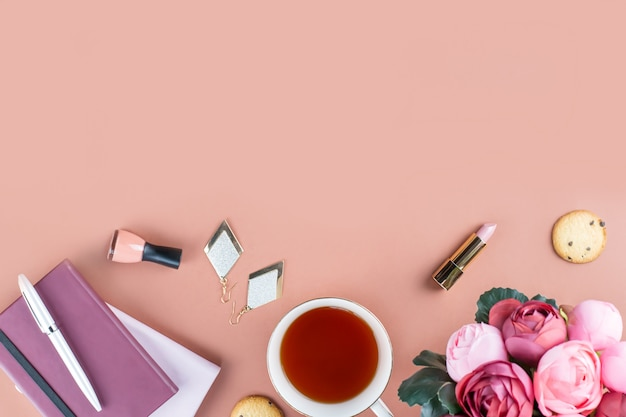 Flat lay home office desk. feminine workspace with diary, flowers, sweets, fashion accessories. fashion blogger concept.