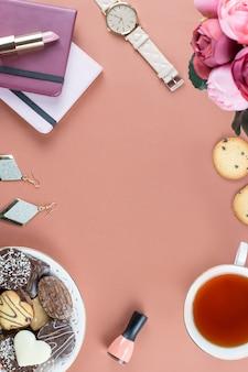 Квартира лежала домашний офисный стол. женское рабочее пространство с дневником, цветами, сладостями, модными аксессуарами. концепция моды блоггер.
