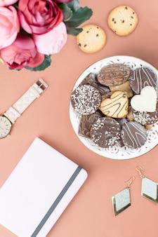 フラットレイアウトのホームオフィスデスク。日記、花、お菓子、ファッションアクセサリーを備えたフェミニンなワークスペース。ファッションのブロガーのコンセプト。