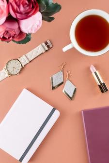 フラットレイアウトのホームオフィスデスク。日記、花、お菓子、ファッションアクセサリーを備えたフェミニンなワークスペース。ファッションのブロガーのコンセプトです。