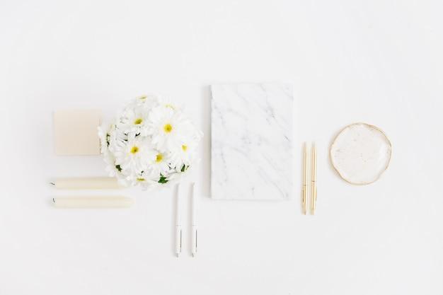フラット レイアウト ホーム オフィス デスク。白い背景にカモミールの花の花束と大理石の日記を持つ女性のワークスペース。上面図