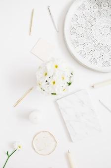 フラット レイアウト ホーム オフィス デスク。白い背景にカモミールの花の花束を持つ女性のワークスペース。上面図