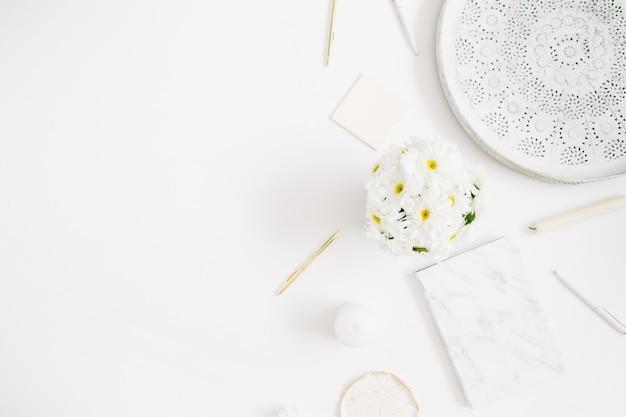 Плоский лежал домашний офисный стол. рабочее пространство женщины с букетом цветов ромашки на белом