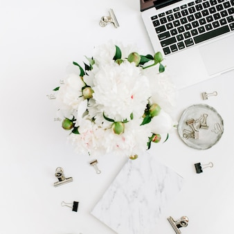 フラットレイホームオフィスデスク。ノートパソコン、白い牡丹の花の花束、アクセサリー、白の大理石の日記と女性のワークスペース