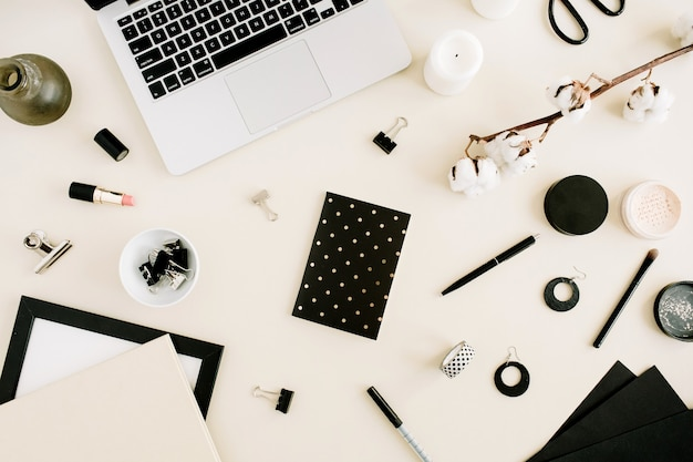 フラット レイアウト ホーム オフィス デスク。薄ベージュの背景にノートパソコン、ノート、綿の枝、アクセサリーを備えた女性のワークスペース