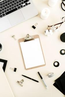フラット レイアウト ホーム オフィス デスク。クリップボードのあるワークスペース、パステルベージュの背景にノートパソコン