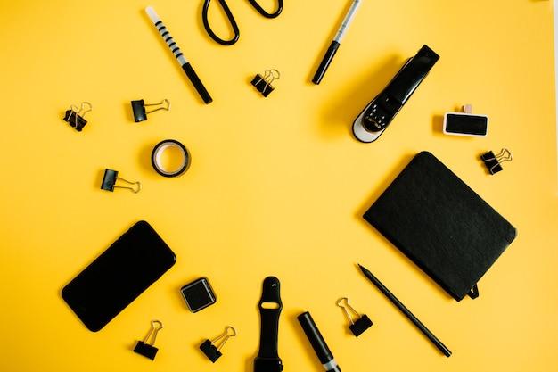 평평하다 홈 오피스 책상. 남성 액세서리가있는 작업 공간 : 일기, 시계, 노란색 휴대폰
