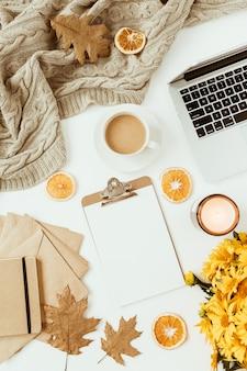 空白のコピースペースクリップボード、花の花束、コーヒーカップ、毛布、封筒、白の葉とフラットレイホームオフィステーブルデスクワークスペース