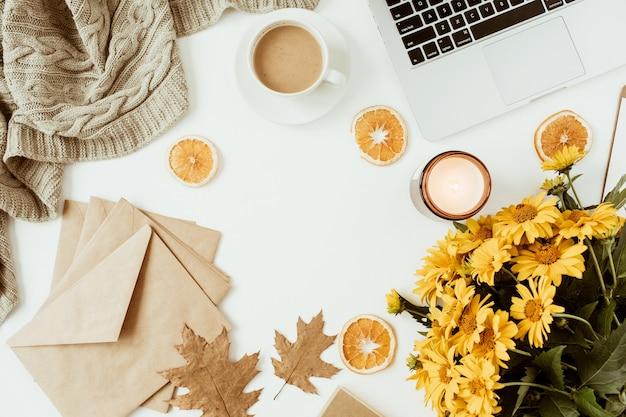 Плоский домашний офисный стол рабочий стол с пустой рамкой для копирования, букет цветов, кофейная чашка, одеяло, конверты, листья на белой поверхности