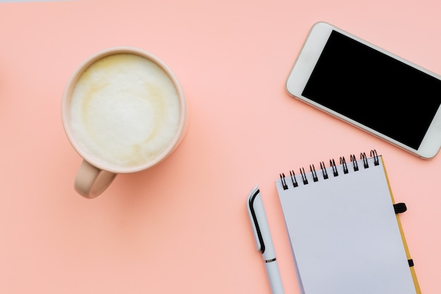 Flat lay home office workspace modern smatphone with cup of coffee and blank notepad, copy space on pink wall