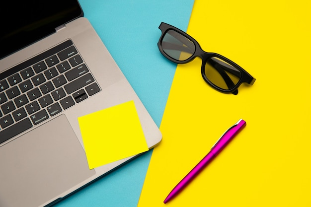 Flat lay of home workplace with laptop, yellow sticky notes, sunglasses and pen