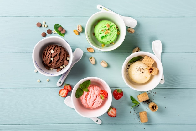 Flat lay of homemade assorted ice cream on light blue wooden surface. healthy summer food concept. top view, copy space
