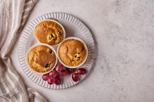 明るい背景のコピーにナプキンとプレート上のチェリーとブドウとフラットレイ自家製カップケーキ