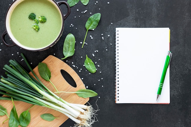 Flat lay homemade soup of broccoli and notepad