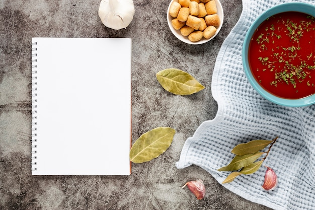 Flat lay homemade soup with notepad