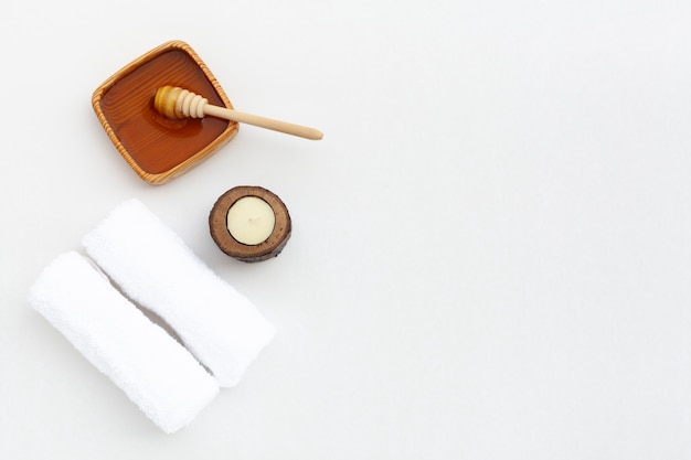 Flat lay of honey and cloth on plain background