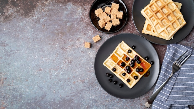Flat lay of honey covered waffles on plate with fruits and copy space