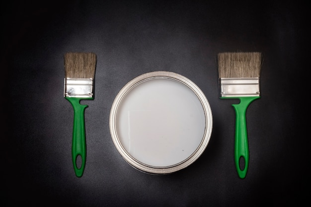 Flat lay horizontally, two green brushes and dishes with paint, on a black textured background with a vignette.
