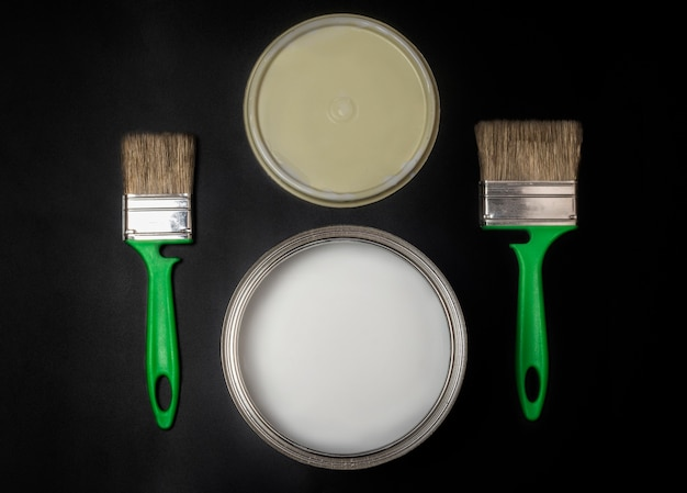 Flat lay horizontally, two green brushes and dishes with paint, on a black textured background.
