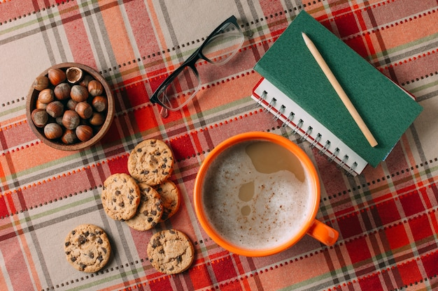 Flat lay of hot chocholate and cookies on cashmere background