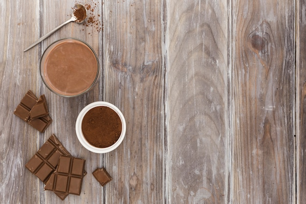 Flat lay of hot chocolate cup with cocoa powder