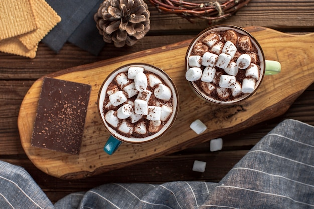 Flat lay hot chocolates with marshmallows and chocolate tablet