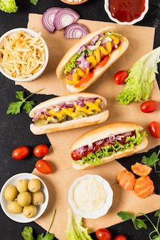 Flat lay of hotdogs on black slate table