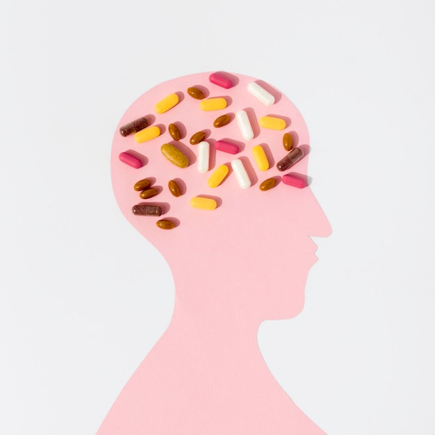 Flat lay of human shape with lots of pills on brain