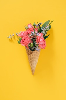 Flat lay ice cream cone with colorful bouquet on yellow, copy space