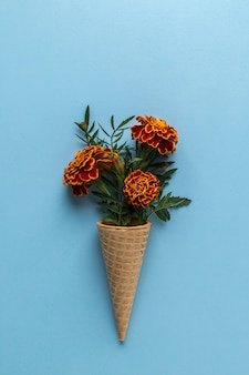 Flat lay ice cream cone with of marigold flowers