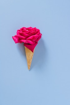 Flat lay ice cream cone with pink rose on blue, copy space