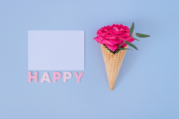 Flat lay ice cream cone with pink rose on blue and white clear blank. happy text