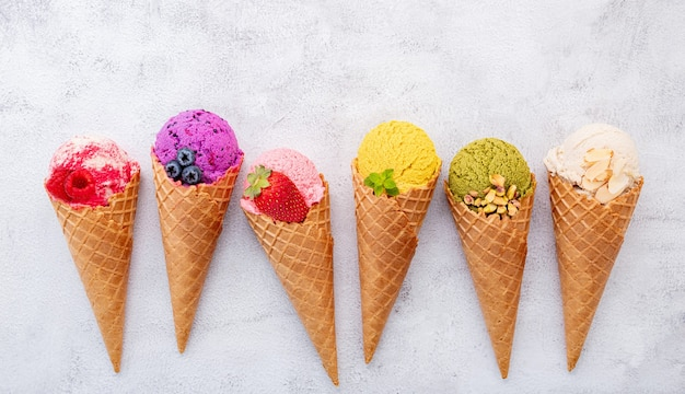 Flat lay ice cream cones collection on dark stone background .