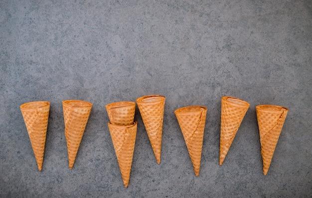 暗い石の背景にフラットレイアウトアイスクリームコーンコレクション。
