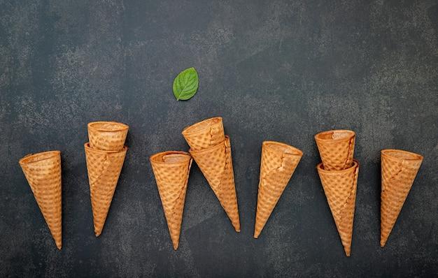 Плоская коллекция конусов мороженого на темном каменном фоне.