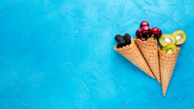Flat-lay ice cream cones with berries with copy space