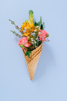 Flat lay ice cream cones with colorful bouquet on blue, copy space