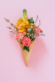 Flat lay ice cream cones with colorful bouquet on pink, copy space