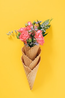 Flat lay ice cream cones with colorful bouquet on yellow, copy space