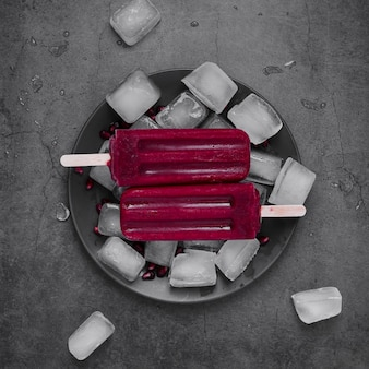 Flat lay ice cream on stick on plate with ice cubes