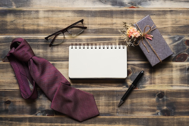 Flat lay image of gift box, necktie, glasses and blank space notebook.