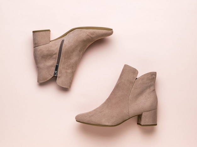 Flat lay image of women's beige half-boots on a beige surface